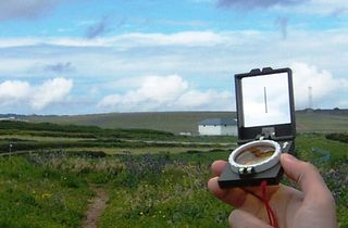 Hand_holding_Compass_against_clouds